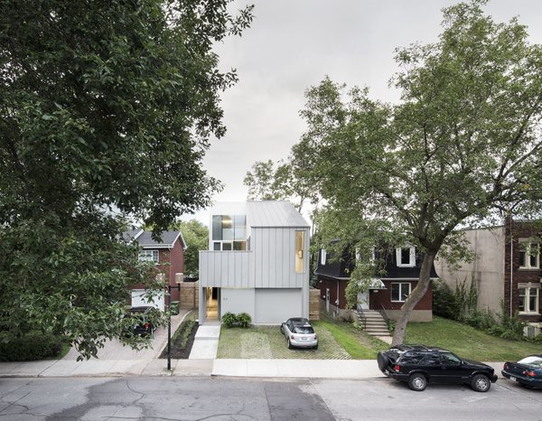 "Located in Montreal, Tuan Vu and Jean François's sleek modern home is designed to balance the need for privacy while maximizing natural daylight. The exterior is clad in a single material to maintain a unified aesthetic. ""We wanted to keep the house light and we wanted to emphasize its overall form instead of its different elements so we found a metal cladding that could work on both the roof and walls,"" says Thomas Balaban, the architect who designed the structure. ""It was very important for us that it be the same material for both. Where we did change material around the entry and the windows, we matched the color of the metal cladding so as not to disturb the reading of the uniform shape."""