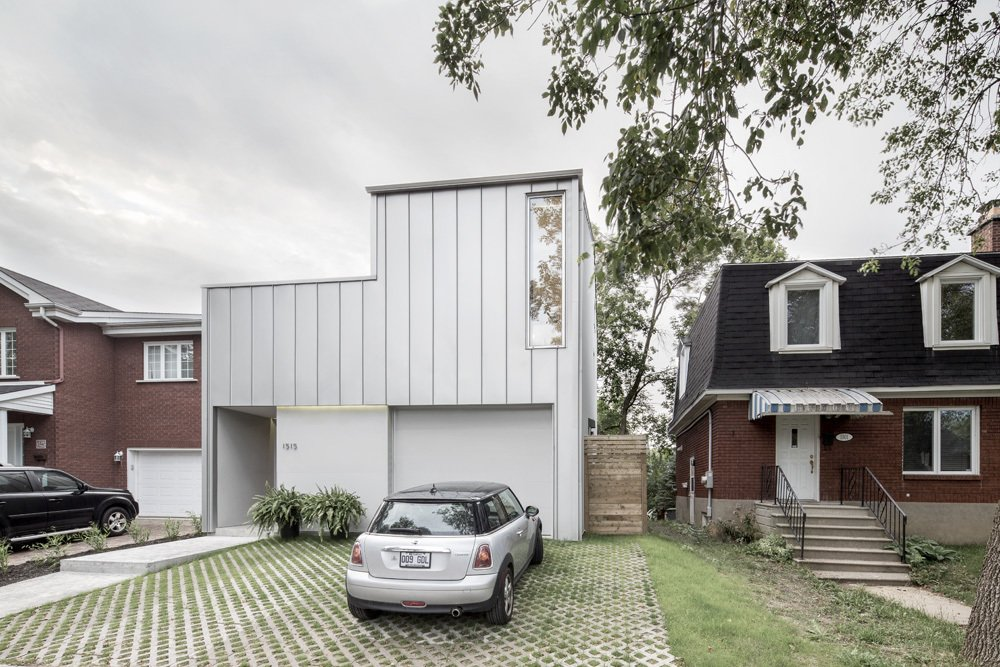 """The house is in a traditional area with strict building restrictions. """"With adjacent houses close to the property line on the east and west sides, the backyard to the north, and narrow side of the lot facing south, the sunny part of the lot was at its center so that is where we put the outdoor spaces,"""" Balaban says. In lieu of a lawn, permeable pavers add a practical and green element to the landscaping.  Exteriors by Matthew Keeshin from A Minimal, Metal-Clad Montreal House With A Hidden Courtyard"""