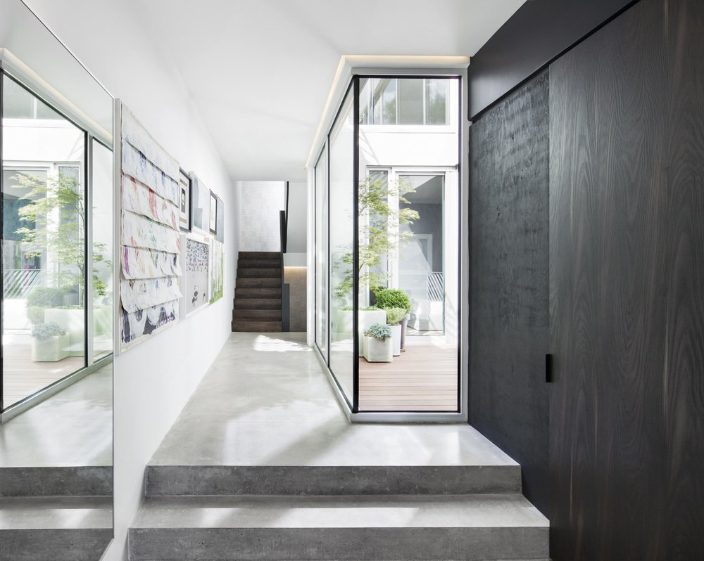 Every room in the house looks onto an outdoor space. Click here to see more modern homes that use courtyards as a design element.  Concrete Obsessed from A Minimal, Metal-Clad Montreal House With A Hidden Courtyard