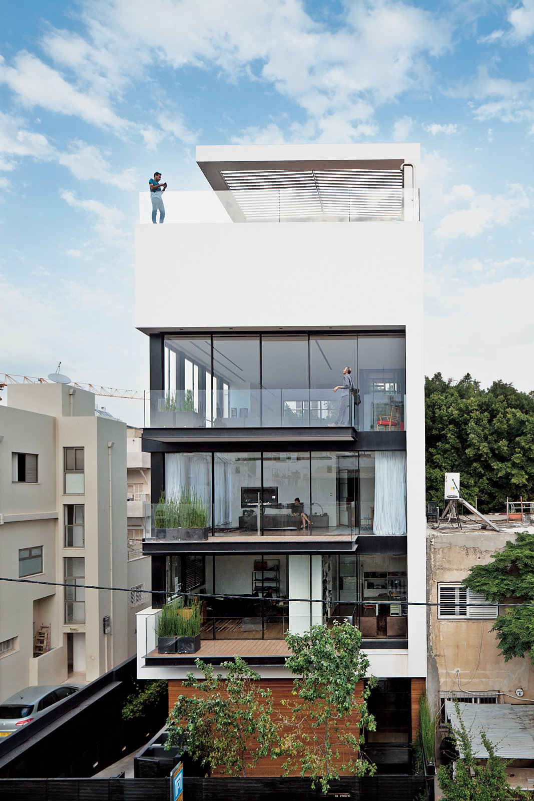 """Exterior, Apartment Building Type, Green Siding Material, Flat RoofLine, and Stucco Siding Material Tall and surprisingly open, the Tel Aviv Town House by Pitsou Kedem Architects continues in the tradition of its Bauhaus-inspired neighbors with a white facade and black window frames.  Search """"our scandinavian style dreams come true brooklyn town house"""" from Modern High-Rise Town House in Tel Aviv"""