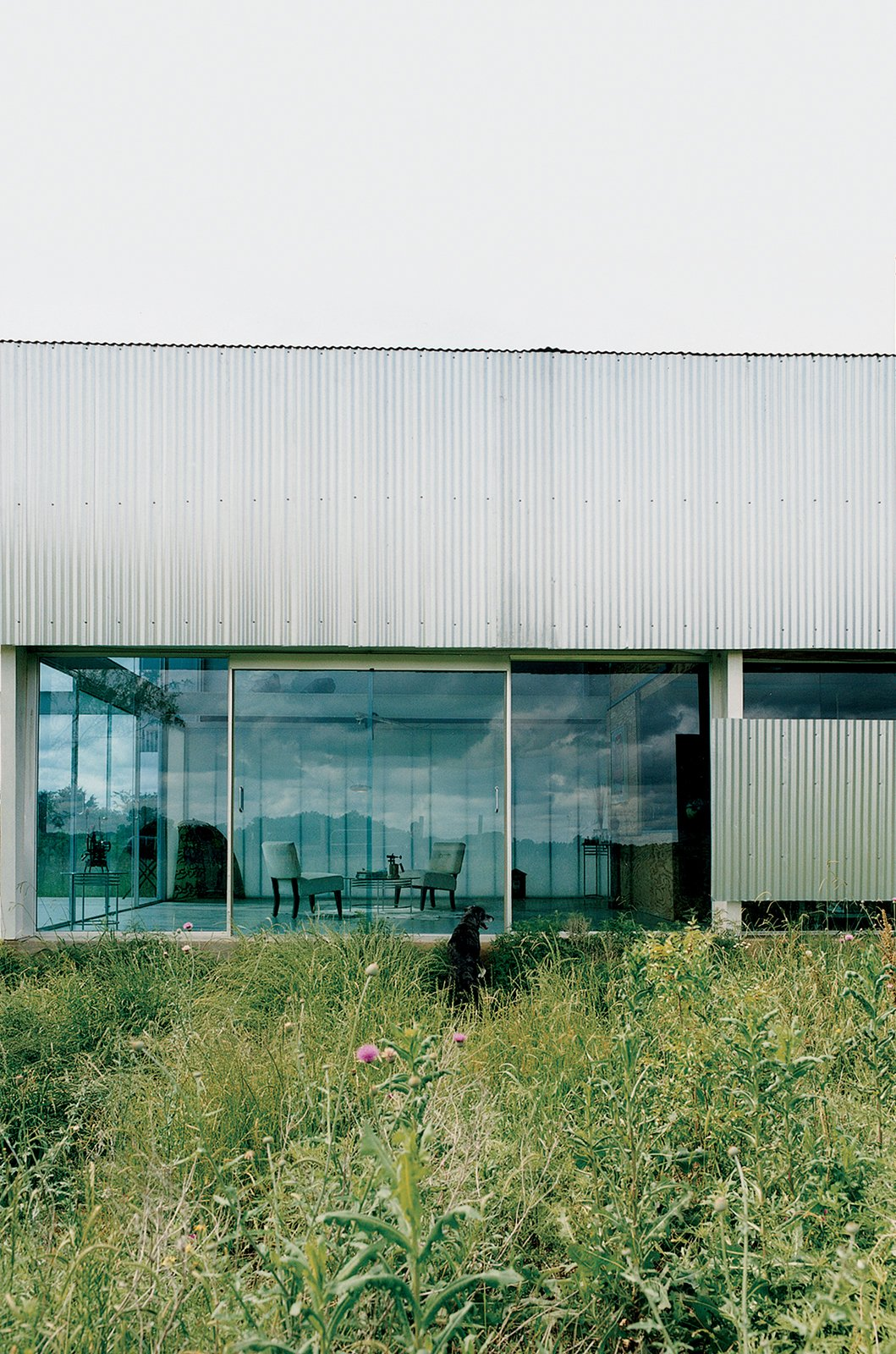 Exterior, House Building Type, and Metal Siding Material The front entrance of the Farley Studio presents a clean, minimalist space—a stark contrast to the colorful clutter of the painting studio hidden behind corrugated-metal walls at the back of the house.  Photos from Lone Star