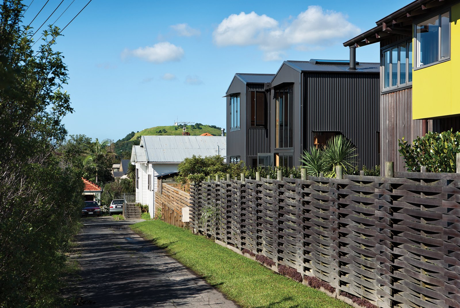 Outdoor, Wood Fences, Wall, and Horizontal Fences, Wall With its pitched roof and verticality, the house blends with the surrounding seaside neighborhood yet remains architecturally distinct thanks to its aluminum cladding.  Material Focus: Corrugated Metal by Diana Budds from Rock the Boat