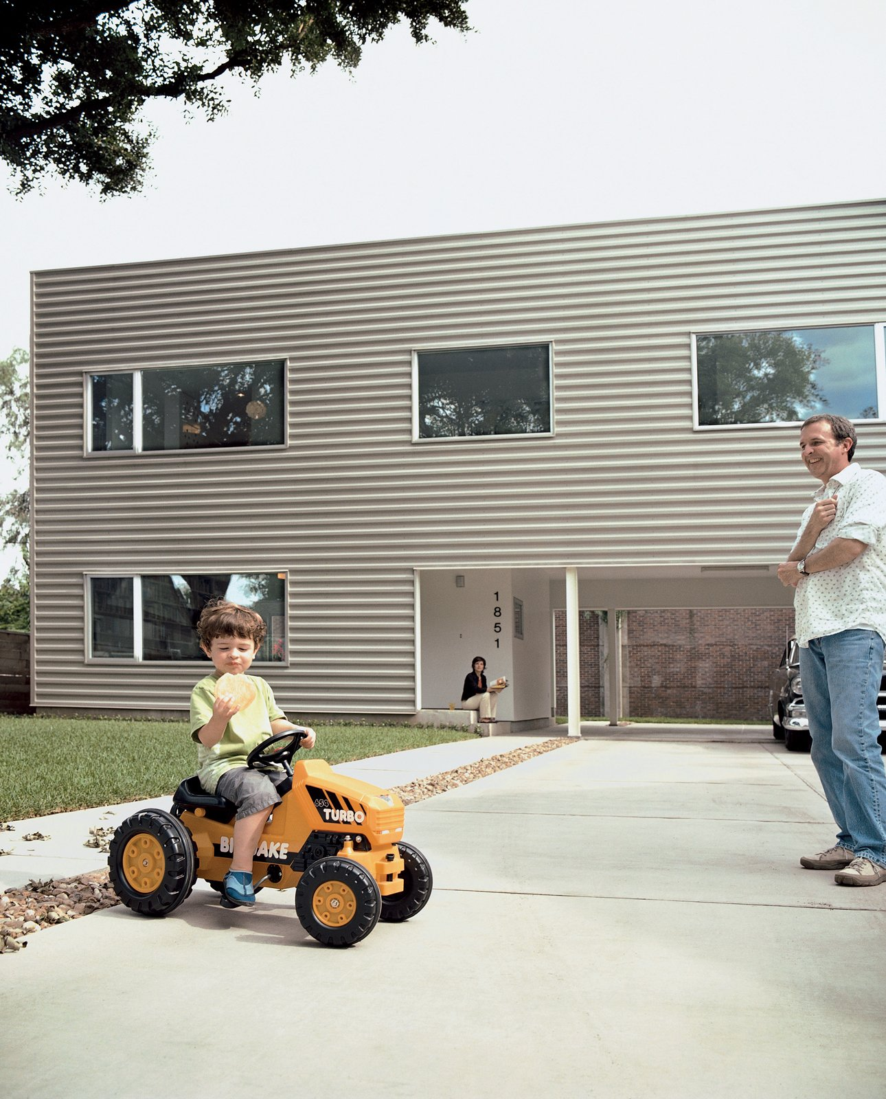 Exterior, House Building Type, Flat RoofLine, and Metal Siding Material Leroy tools around on his mini turbo tractor while munching on a gigantic cookie; his parents look on with envy.  Photos from Houston, TX