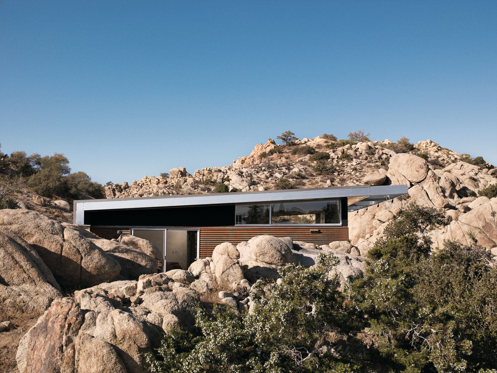 """Outdoor, Desert, Boulders, Trees, and Shrubs For all its hard environmental work, one of the most immediate of the Blue Sky Home's pleasures is how it sits so snugly in its desert surroundings.  Photo 3 of 23 in 20 Desert Homes from Small """"Hybrid Prefab"""" Home in the Desert"""