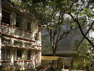 Somewhat by chance, the apartment building's aluminum core references the perforations of the house next door; its interior breezeways also echo those of the neighboring structure.