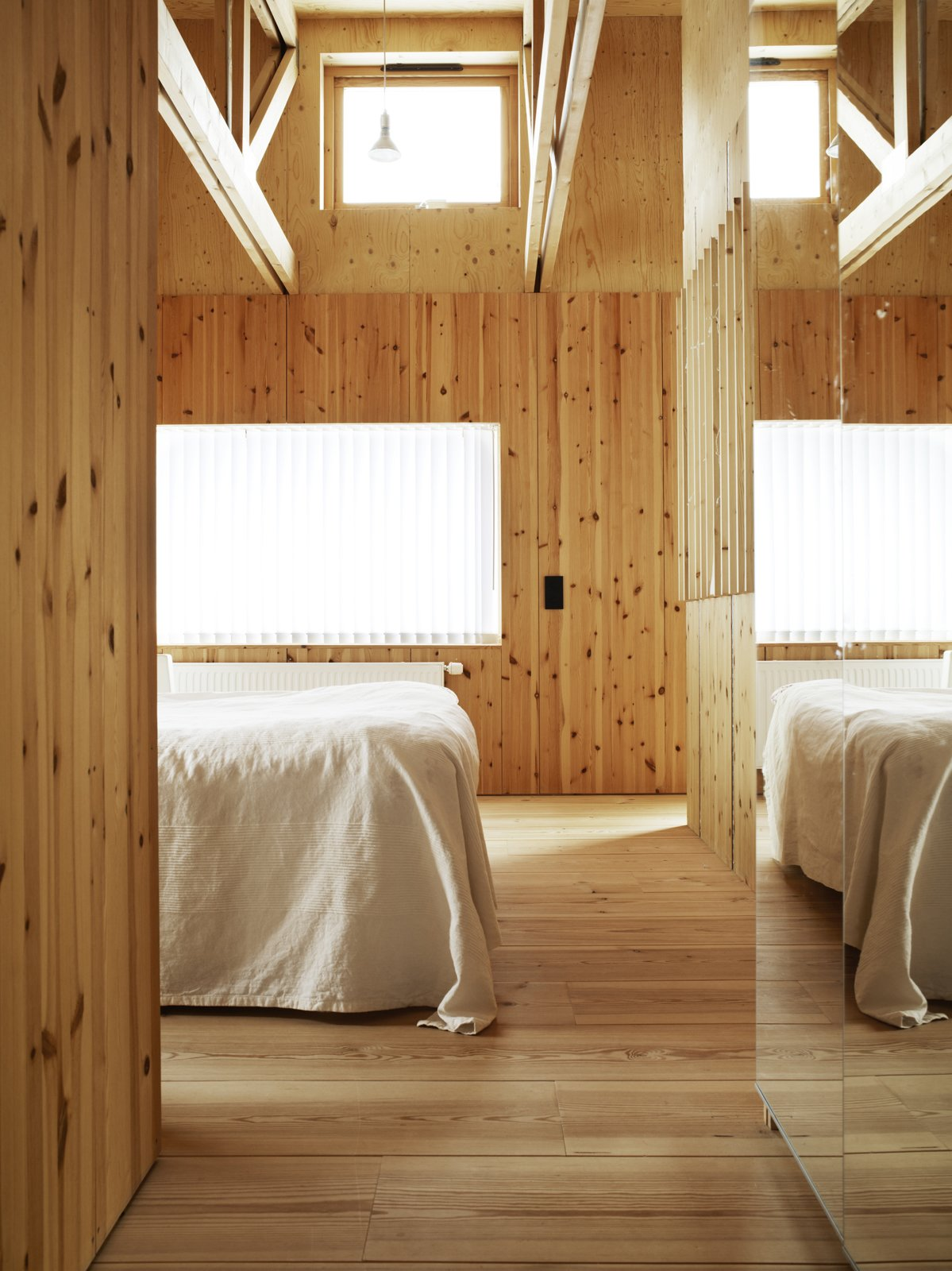 Bedroom, Light Hardwood Floor, Bed, and Pendant Lighting The white linens appear almost ghostly against the natural grain of the wood and muted glow of the window's winter light.  Photo 9 of 11 in 10 Warm Wood Floors from Knotty by Nature