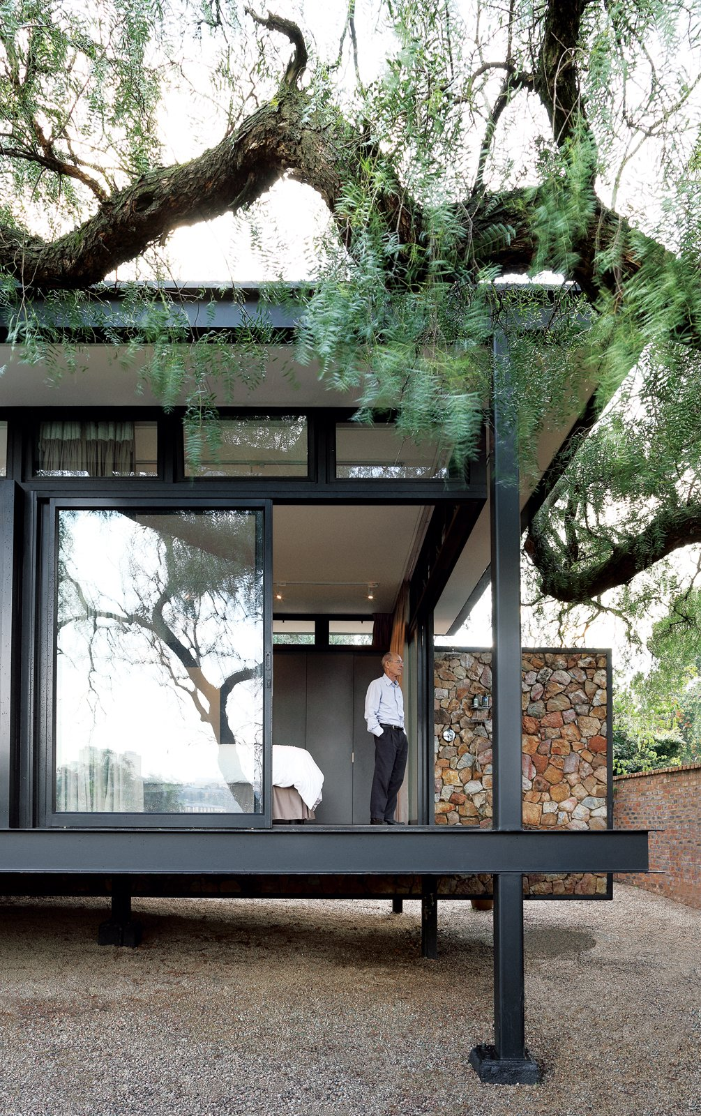 Exterior, House Building Type, Metal Roof Material, and Metal Siding Material Architect Georg van Gass adds a delicately poised cantilevered exterior wall that appears to slice the deck in half. Photo by: Elsa Young  Photo 1 of 1 in A Mies van der Rohe-Inspired Cottage in Johannesburg