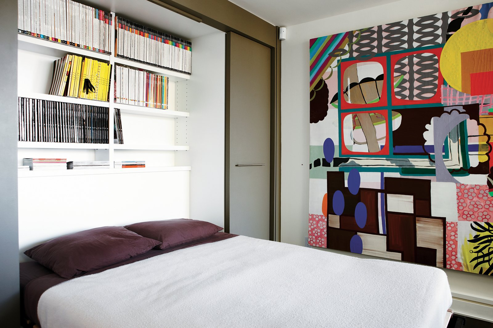 Bedroom, Bed, and Shelves Montague's office doubles as a guest room thanks to a Murphy bed that folds out to reveal shelves stocked with design magazines. The painting is Untitled (Corner Rainbow) by Elizabeth McIntosh.  Bedrooms by Dwell from Party-Friendly Apartment in Toronto