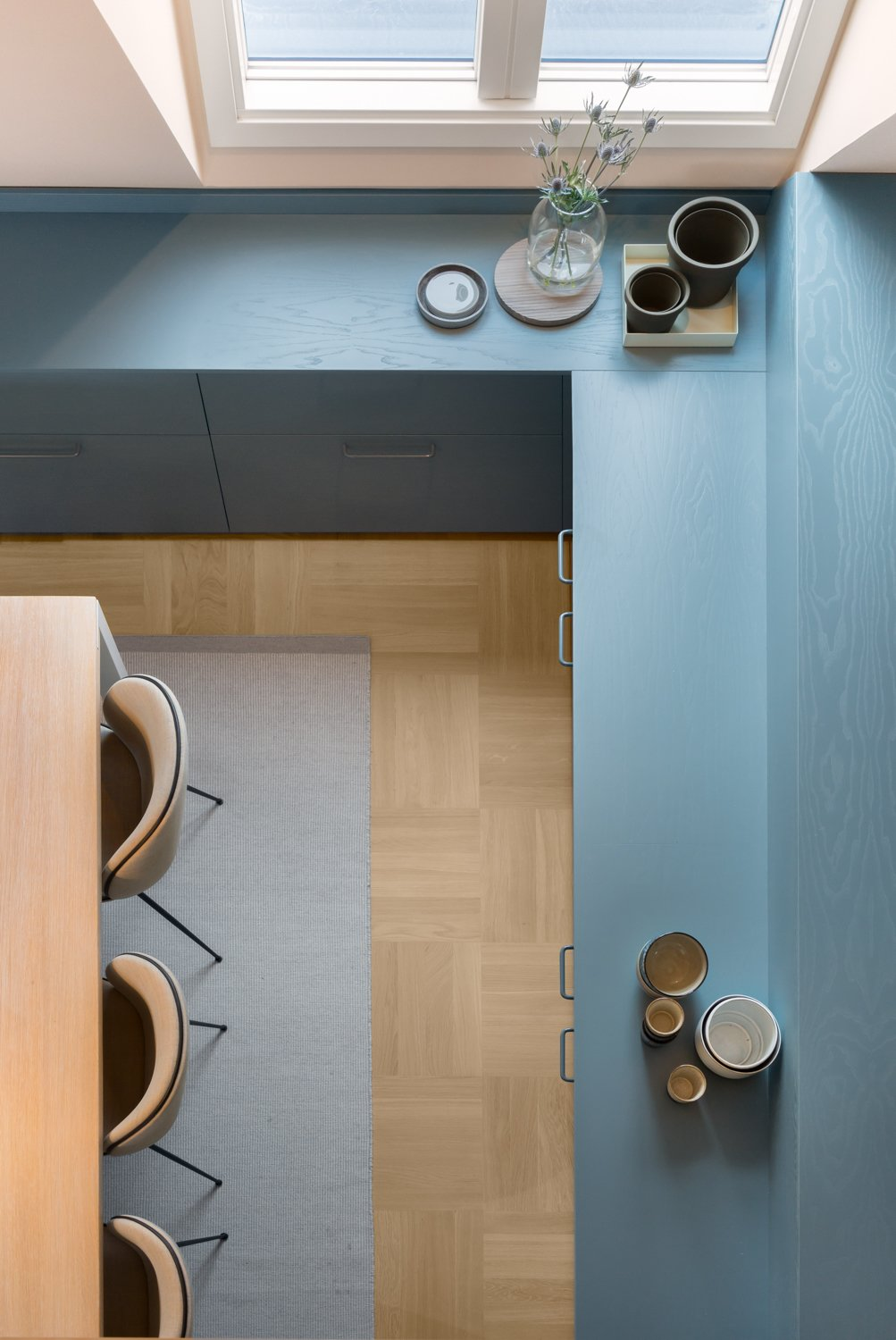 "A custom blue-gray built-in storage unit, which includes shelving, cupboards, and drawers, runs throughout the home, connecting the rooms. ""The tone is calm and creates a dark base,"" Wåhlin says. ""The apricot pink, together with the sandy colors, reflect light but give a warmth to the space and contrast with the blue tones. Together, they become dynamic.""  Sweden from There's Not a Single White Surface in This Comfy Stockholm Loft"