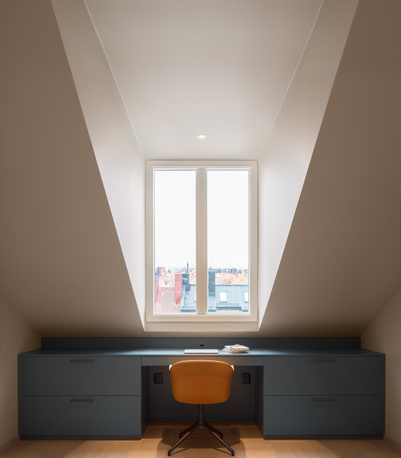 In one of the three upstairs bedrooms, a Muuto chair is flanked by a built-in desk with deep drawers that take advantage of the room's distinctive angles.  Loft