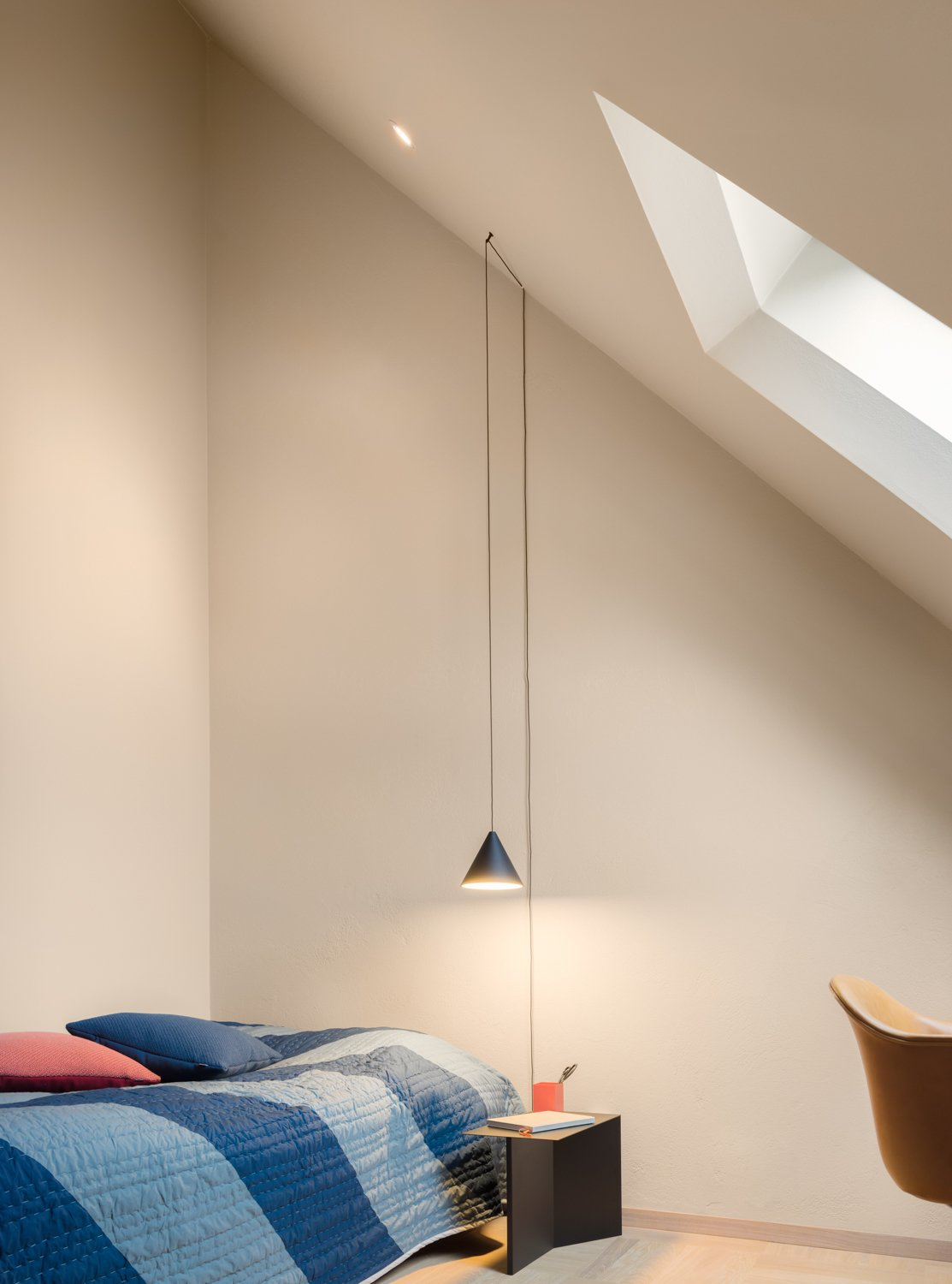 Illuminated by a String Light from Flos, the bedroom embraces the loft's palette with a side table, duvet, and pillows by HAY.  Bedroom from There's Not a Single White Surface in This Comfy Stockholm Loft