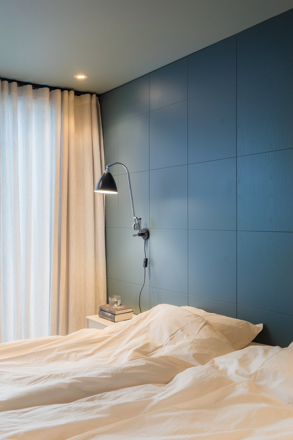 Bedroom, Night Stands, Wall Lighting, Recessed Lighting, and Bed NOTE designed the wood blue-gray wall covering in this bedroom. A chrome Bestlite BL6 wall lamp by Gubi hangs near custom-made curtains, created using fabric by Astrid.  Bedroom
