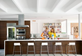 The once-hermitic kitchen now has a direct view of the patio and pool. The hood is by Zephyr, the cooktop is by Miele, the refrigerator is by Sub-Zero, the ovens are by GE Monogram, and the stand mixer is by KitchenAid.The Sebastian barstools and Trådig fruit bowl are also from Ikea.