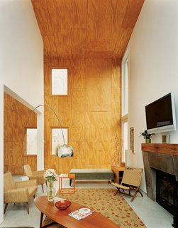 The double-height living area features unfinished plywood cladding treated with linseed oil.