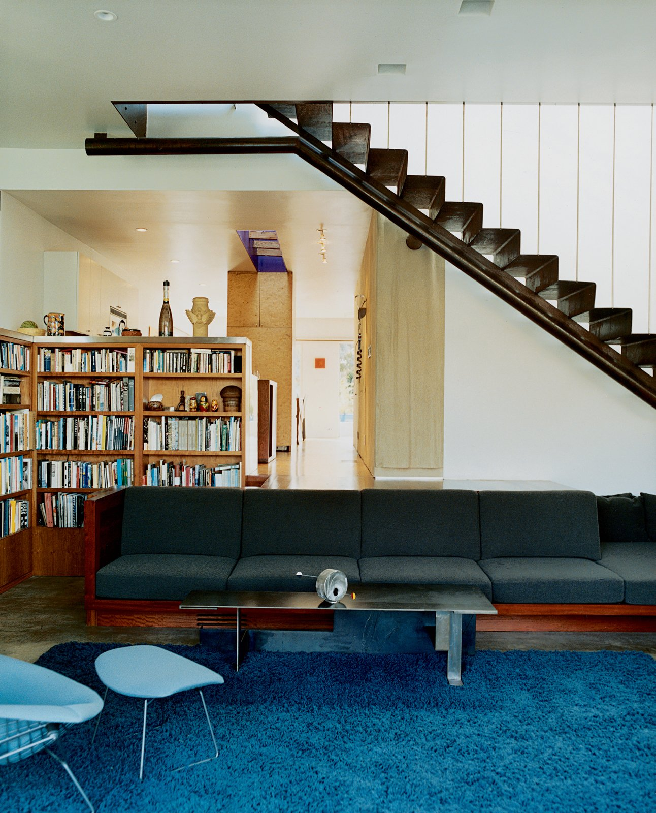 Living Room A built-in sofa with Design Tex upholstery marks the boundary between the two-level addition and the bungalow. Leading up to the master bedroom, a perforated metal staircase, lit from above, casts a Sigmar Polke–like shadow grid on the concrete floor.  190+ Best Modern Staircase Ideas from Solar Inspiration