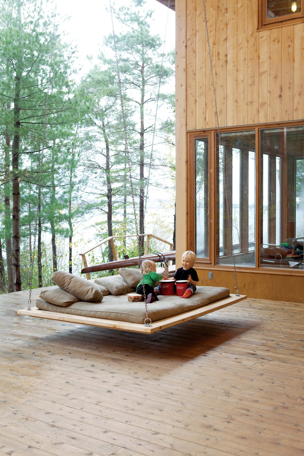 "Outdoor, Large Patio, Porch, Deck, and Wood Patio, Porch, Deck Two-year-old Annika and five-year-old Soren make music on the ""nap swing,"" a popular hangout spot for kids and adults alike.  Backyards & Decks from Four Friends Joined Forces to Realize This Idyllic Forest Retreat Outside Toronto"