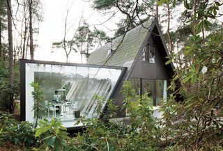 A glazed extension to Rini van Beek's home just outside Antwerp, Belgium makes an old holiday A-frame home more suitable for permanent living.