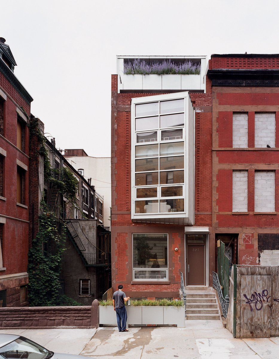 """Yvette Leeper-Bueno and Adrian Bueno's home, on West 112th Street in New York City, is recognizable by its two-story bay window angled to bring light and views into the dark, narrow structure. """"There's a threshold of planting between the outside and inside,"""" says architect Laura Briggs, citing the blooming boxes on the sidewalk, the rear deck, and the master-suite terrace (above the bay window). Photo by Adam Friedberg. See how the rooms stack up inside the narrow shell.  New York City Row House Renovations We Love by Zachary Edelson from Exterior Stairs"""