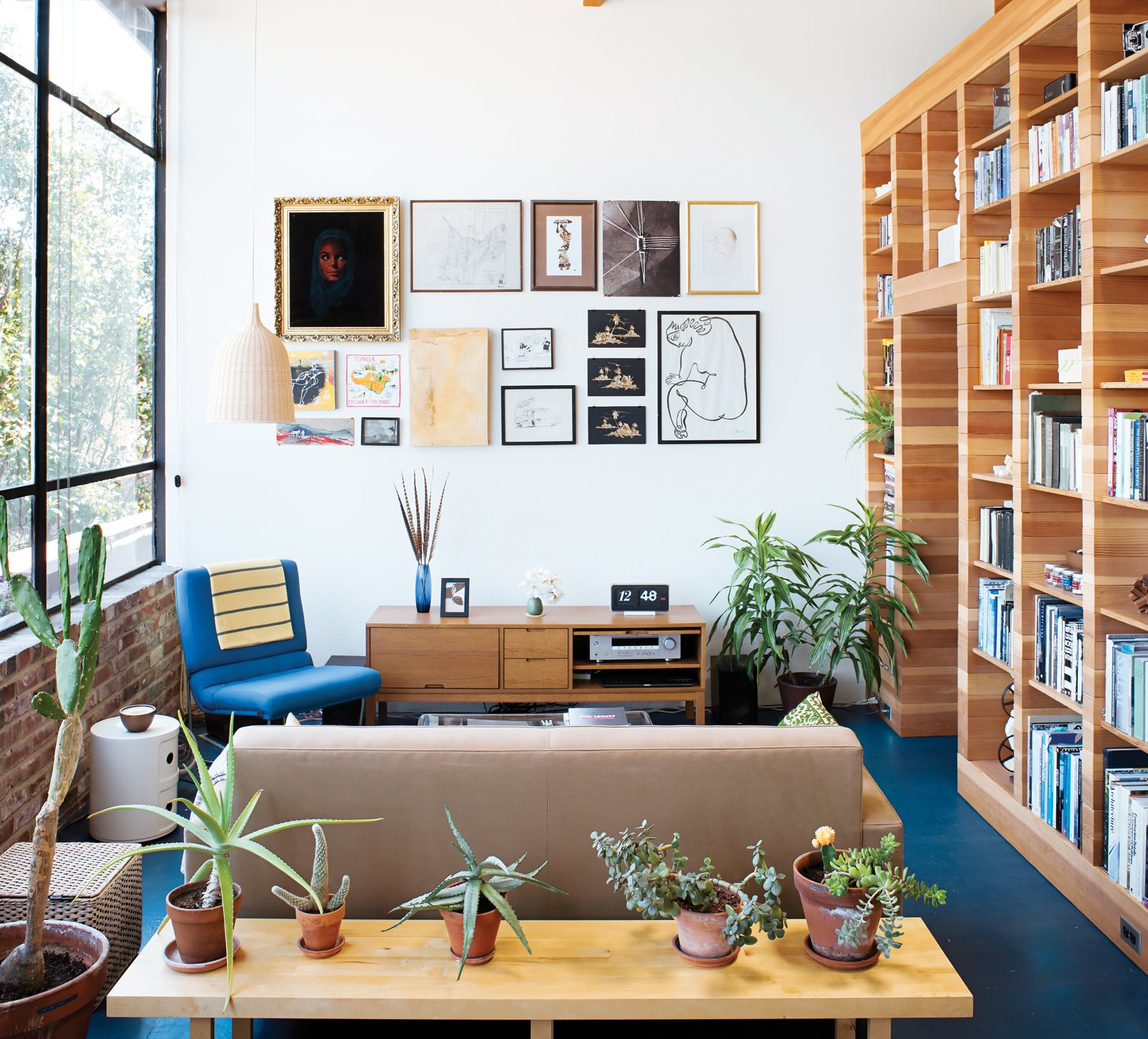 """Living Room, Bookcase, Shelves, Pendant Lighting, Sofa, Chair, Media Cabinet, End Tables, Bench, and Linoleum Floor The picture wall is adorned with images collected from family, colleagues, and estate sales. """"I kill plants, so cacti are our friends,"""" Peter says of the succulents along the low table behind the Design Within Reach sofa, just over which an Established & Sons Font clock keeps time.  Search """"how giant windows"""" from Storage Savvy Renovation in Emeryville"""