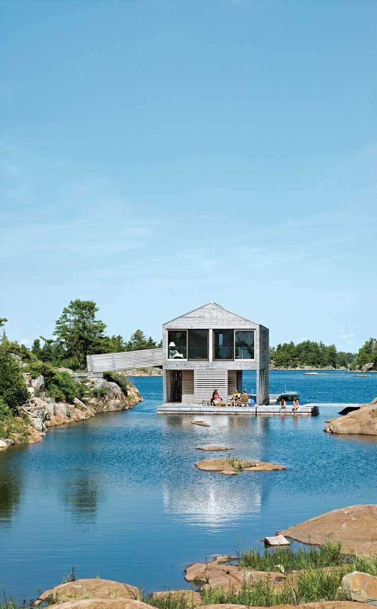 """Exterior, House Building Type, Cabin Building Type, and Wood Siding Material Cedar slats mark the facade of Floating House, Doug and Becca Worple's lake house in Ontario. The architects, MOS, chose materials and shapes that wouldn't stand out. """"They're really simple, almost Platonic forms,"""" principal Michael Meredith says. The modest cabin has boat, a gabled roof and a cladding of untreated cedar, a material that shows up on docks and homes along Georgian Bay. """"Allowing the buildings to weather seems the right thing to do,"""" Sample says. And it's ready for winter: Sliding barn doors seal the place up as an impenetrable box.  Photo 79 of 101 in 101 Best Modern Cabins from Nautical Abodes"""