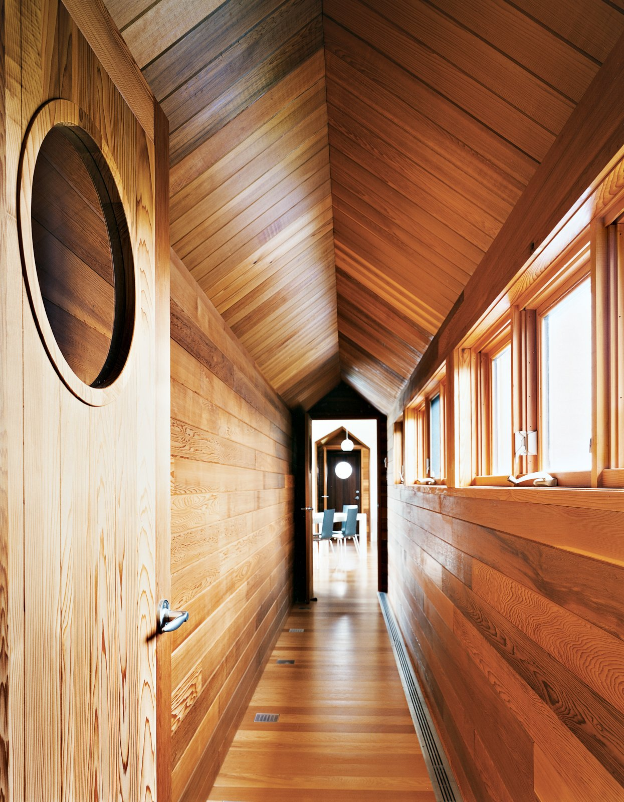 Hallway and Medium Hardwood Floor The view from the master bedroom down the long cedar corridor into the living room is one of the home's real pleasures.  Hail Cedar: 7 Houses that Make Use of Cedar Wood by Diana Budds from Blue in the Facade