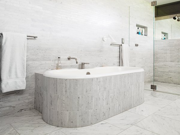 In the master bathroom, Chris clad the tub and walls in Carrara marble. An AJ Wall sconce by Arne Jacobsen for Louis Poulsen sheds some light on bathtub reading.