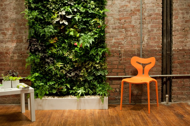 Living Room, Table, Chair, and Medium Hardwood Floor Plant Wall Design created a custom, self-sustaining vertical green wall for the show.  Photo 3 of 10 in Living Green Walls 101: Their Benefits and How They're Made from Modern Building Materials at Dwell on Design NY