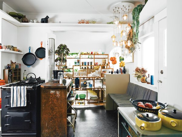"""Designer Omer Arbel develops his latest works inside an eclectic Vancouver home filled with a teeming assortment of pets and prototypes. Hanging over the bench is our first Bocci 14 light fixture. I feel like it would be bad luck not to have it in the house. Other pieces in the kitchen—like the wooden island Aileen found in an alleyway and the yellow ceramics by Knabstrup, a Danish company active in the 1960s—we've collected along the way."""" Photo by José Mandojana."""