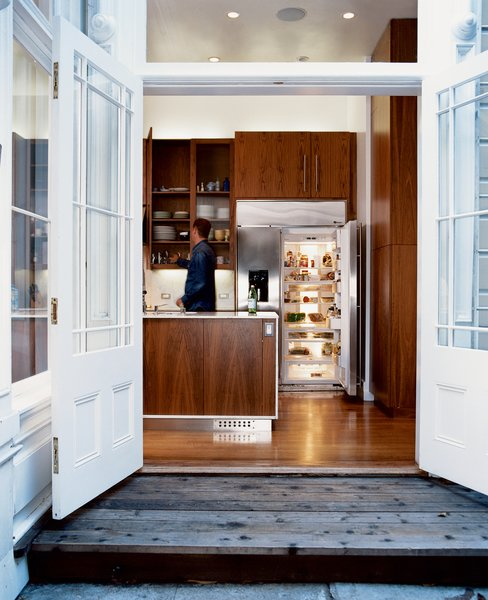 The walnut cabinets in the kitchen, which update and warm the space, were designed by Nilus de Matran and fabricated by George Slack.