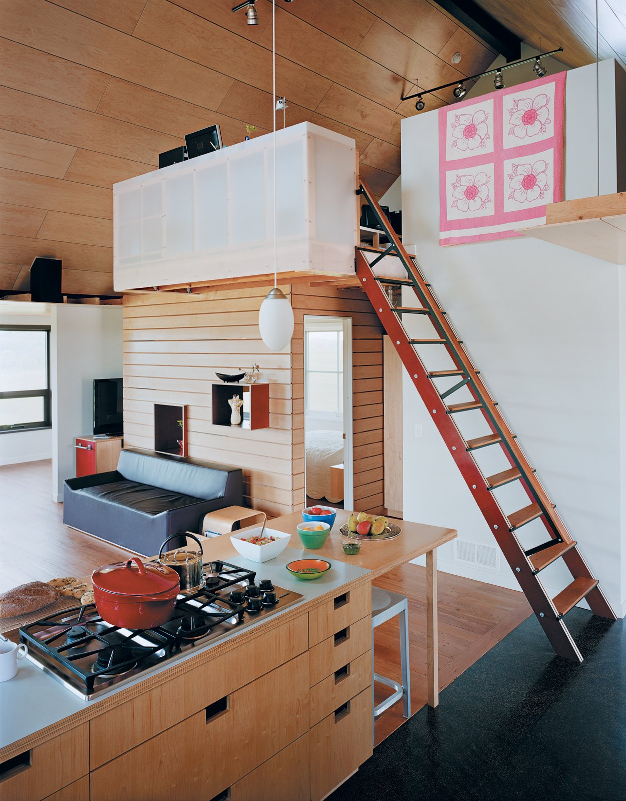 Kitchen, Wood Counter, and Cooktops The kitchen cabinets with cutouts for handles were designed by a local woodworker. The stairs lead to a loft office where Joanna works, perched beside a quilt made by her great-grandmother.  Blu Dot Spotted from Farm Fresh