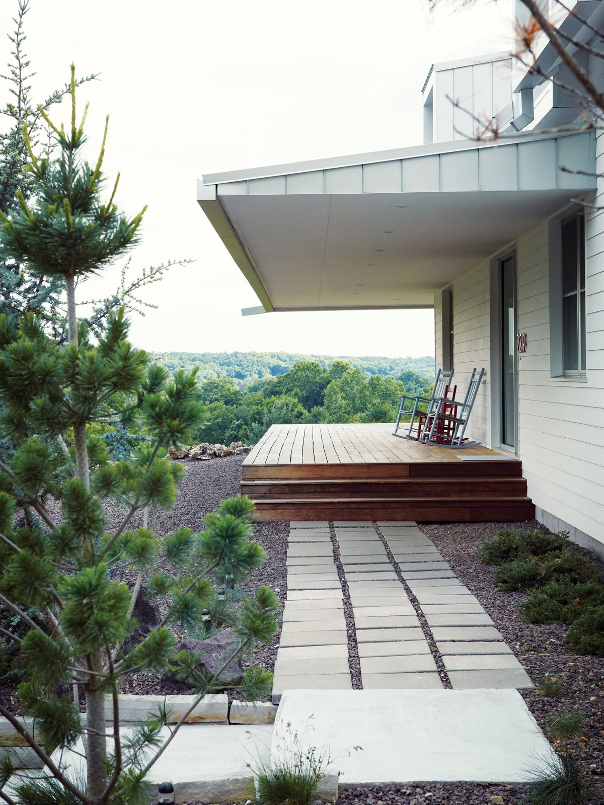 Outdoor, Pavers, Wood, Walkways, Trees, and Hardscapes MODERN TAKE ON A TRADITIONAL FARMHOUSE IN MISSOURI  Thanks to Matthew Hufft, their envelope-pushing architect and longtime friend, Hannah and Paul Catlett have a new home in southwestern Missouri that's a fresh, unconventional take on the traditional farmhouse. The homeowners call the house Porch House after it's majestic wraparound porch.  photos by: Joe Pugliese  Best Outdoor Pavers Wood Photos from Ozark Original
