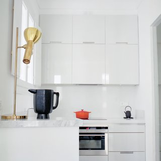 "Hayon and Klunder's kitchen is all white, down to the minimalist, lacquered Santos cabinets. When it comes to picking paint and fabric colors, Hayon advocates for grayed-out hues. ""My recommendation is that even when you use bolder colors make sure they have a percentage of gray in them,"" he says. ""If you use yellow, it should be yellow-gray. If a green is used it should be a green-gray."""