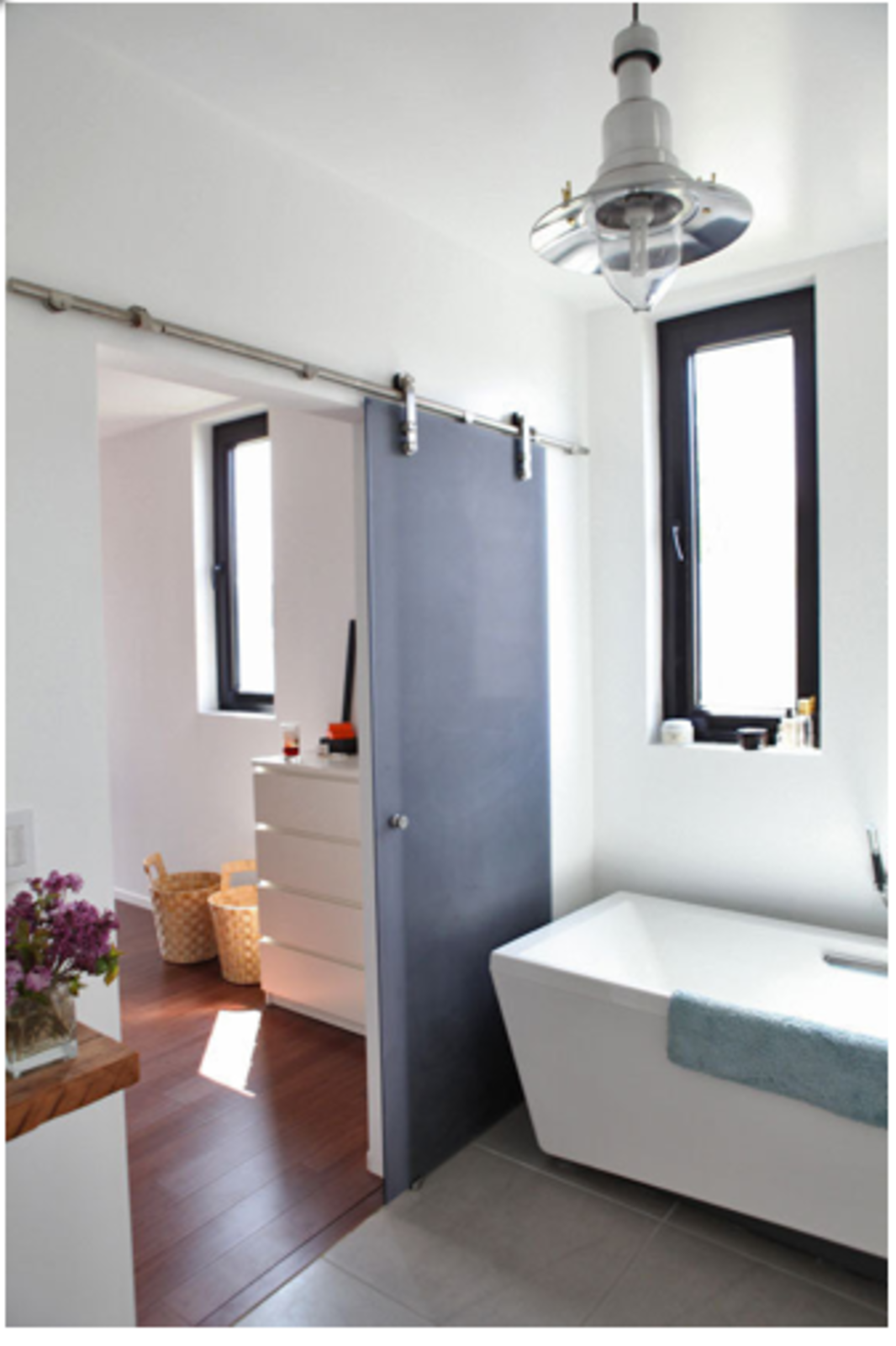 Translucent sliding doors with exposed hardware increase bathroom space and light.  Space-Saving Sliding Doors by Erika Heet from A Modern House on a Budget in Los Angeles