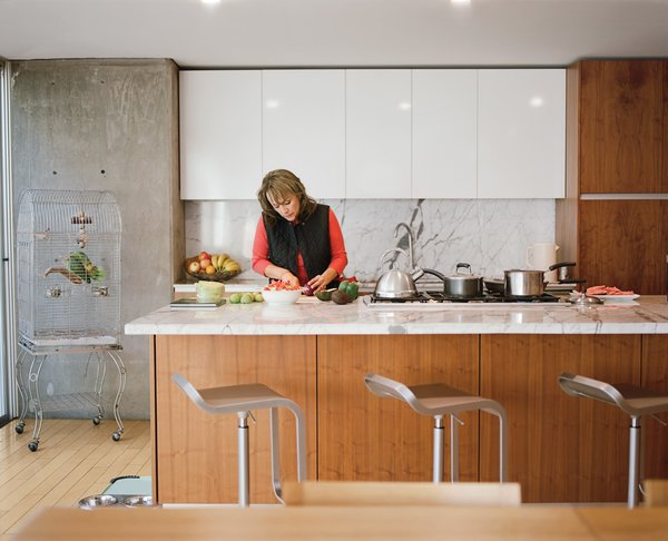 Angelica Becerril prepares food at the kitchen island; the Carrara marble countertop is one of the few luxury materials used in the house.