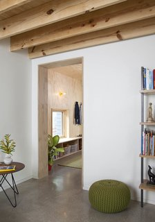 """""""One thing that is highlighted by this project—and what I'm most interested in—is creating great architecture for limited means,"""" Guess says. """"When someone comes to me with constraints, I always feel like there's a better outcome in the end."""" The pouf, side table, and bookshelf are from CB2."""