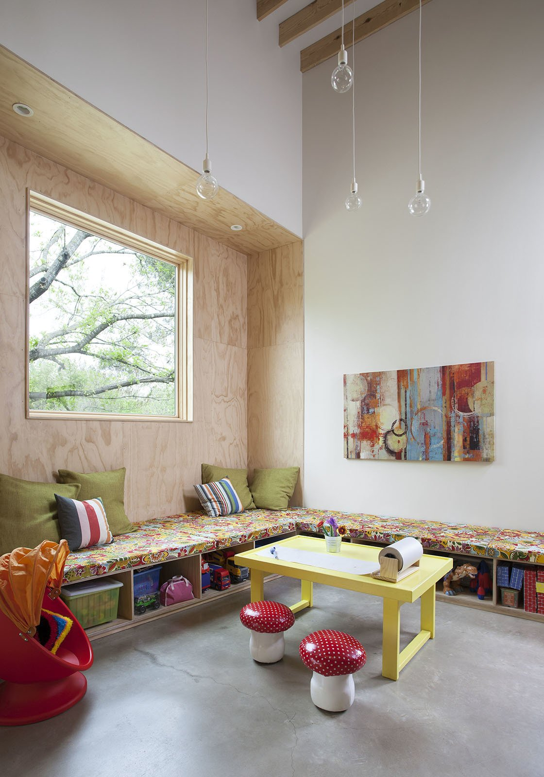 "In the playroom, built-in casework offers storage for toys. The yellow table was custom-built by the Kristin's father. The clear pendant lights are by Muuto. The ""toy zone"" is adjacent to the kitchen so that Lowell and Kristin can prepare meals and keep an eye on their yound children, aged three and five. ""The residents wanted as little freestanding furniture as possible,"" Guess says. 'We did a lot of benches, which are made out of plywood so they're fairly inexpensive.""  Inviting Kitchen Built on a Tight Budget by Diana Budds"