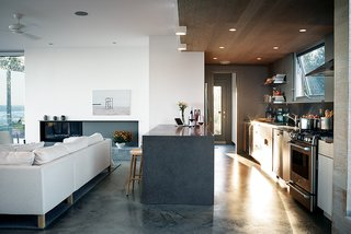 The cabinets above are from Ikea, the range is by GE, and the Jenn-Air refrigerator is tucked unobtrusively into the pantry wall. The troweled concrete floor was poured in place by builder Peter Knudsen.