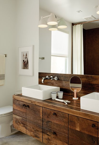 Builder Luke Gilligan of Gilligan Development used reclaimed oak planks from a deconstructed barn to create this modern bathroom vanity's rustic millwork. To achieve the rugged look, he sanded and wire-brushed the wood, then applied a clear stain. The sinks are from Duravit's Vero line and the cabinet pulls are from Top Knobs.