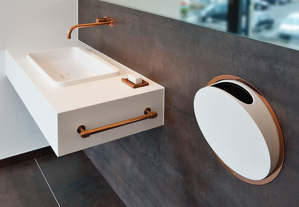 Bath Room and Wall Mount Sink In 1968, Danish architect and designer Arne Jacobsen designed the 112 faucet and mixer series and a line of in-wall accessories for Vola. In 2014, the Danish company updated the classic design by adding a deep copper finish.