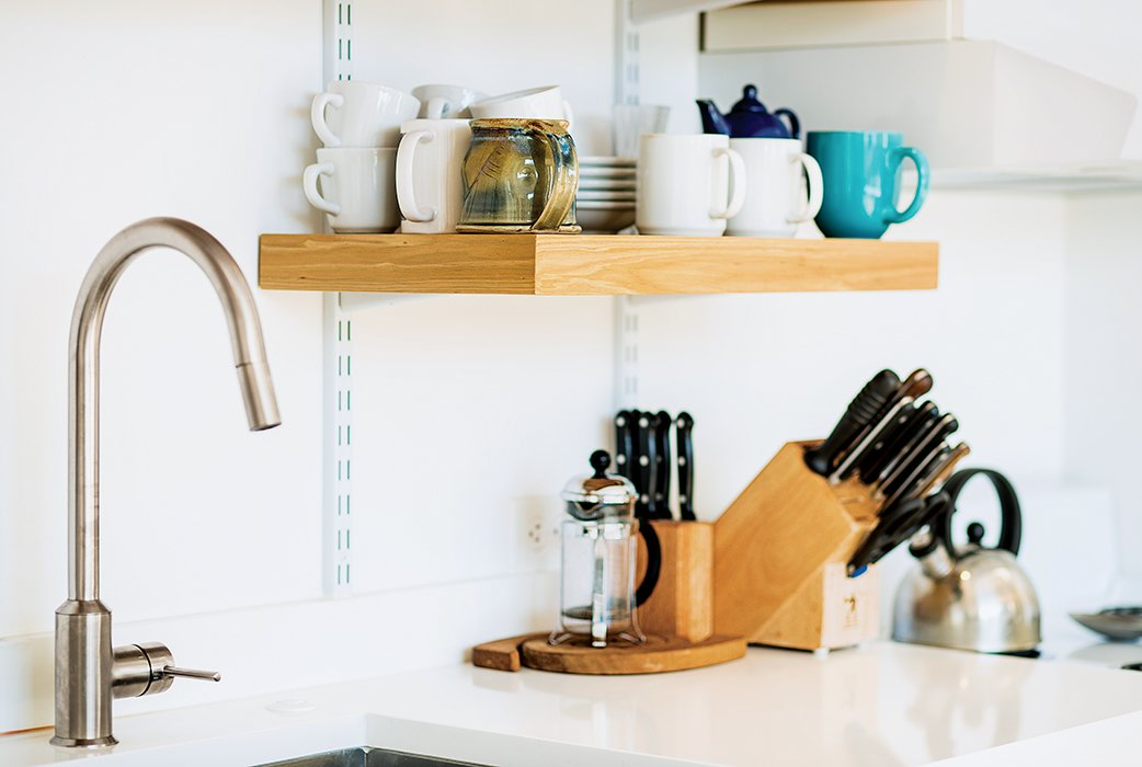 Kitchen and Undermount Sink C & G Construction made the kitchen shelving from reclaimed cypress not used in the siding and decking. The White Cliff countertops are from Cambria, and the faucet is from Ikea.  Photo 9 of 12 in A Versatile House Fulfills All This Musician's Needs