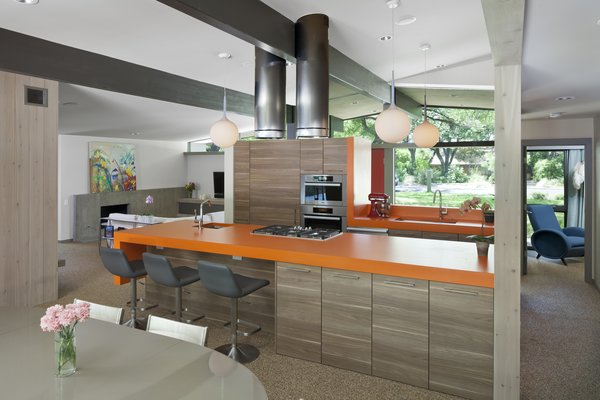 The architects went with a bold, orange hue for the kitchen countertops. Past the front door and a short hallway lies an expansive living, dining, and kitchen space.