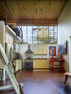 The kitchen and living area occupies the ground level of the double-height interior while a sleeping loft is above. Hoover salvaged the kitchen cabinets from a project her contractor, Schuchart/Dow, was demolishing. The floor is masonite, the ceilings are plywood, and the walls are drywall. Polycarbonate panels usher light in from the clerestory windows.