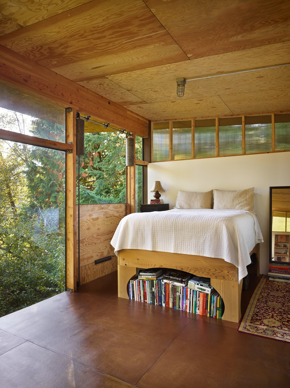 """Bedroom and Bed A door next to the bed drops down, opening the room to its surroundings. """"It's a fantastic way to ventilate the space, but also makes sleeping in the loft feel like camping when it's down,"""" Eerkes says.  Bedrooms by Dwell from An Eco-Friendly Compact Cabin in Washington"""