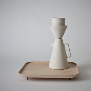 The patterns are hand-engraved into the ceramic, emphasizing the uniqueness of the pieces. The tray is made of Canadian maple wood, a nod to Mjölk's home base. The cups can be stacked on top of the pitcher, giving the set a whimsical quality.