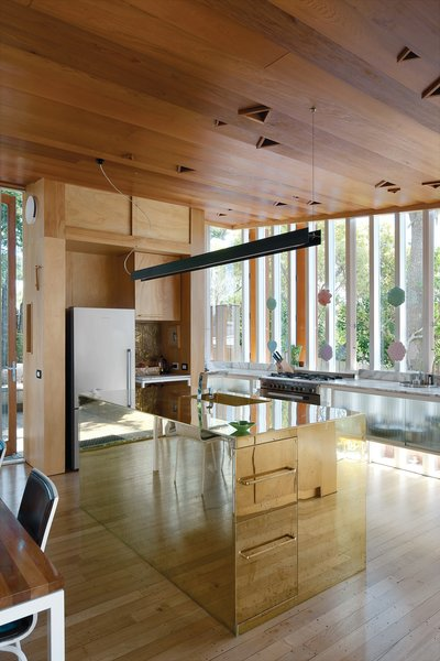 the reflectivity of the brass kitchen island makes it seem to dematerialize.