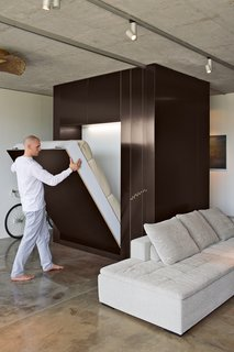 A common trend among modern Murphy beds is to fold into a cabinet. By lowering the custom Murphy bed and rolling a sliding plywood door, this homeowner creates an instant guest room.