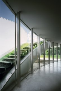 The expansive open-air living room on the first floor is framed with a curving wall of windows. The glass wall works as an outdoor atrium looking out on an exposed   sod-covered staircase and allows the room to be bathed in natural light.