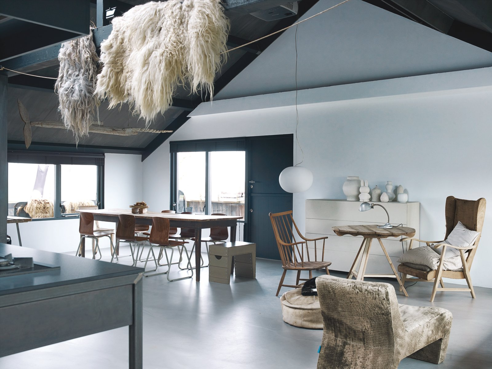Leen and Middendorp's living space is peppered with an assortment of objects and textures, including sheep's wool, an antique French farmhouse table, salvaged chairs, a Glo-Ball light by Jasper Morrison for Flos, and an Axel leather sofa by Gijs Papavoine for Montis.  Photo 2 of 15 in Rural Home on a Holland Harbor