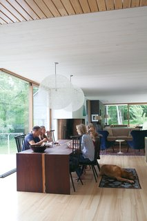 The family relaxes in their home's dining   room, sited atop the old foundation. Organschi designed and fabricated the table of wenge wood; the chairs were inherited from his uncle; and the pendant lights are Bertjan   Pot designs for Moooi.