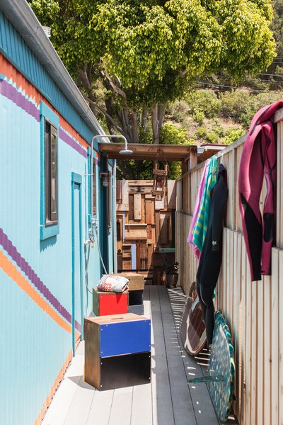 Once a classic trailer-park scheme of mint green and white, the exterior of Commune Images owner Sofie Howard's 500-square-foot Malibu trailer was distinctively repainted. The gate is a patchwork of scrap wood pieces. Partly inspired by 1970s Vans slip-ons, Howard's boyfriend, artist Grant Shumate, painted accent lines on the side of the trailer. The porch houses a seating area with handmade MORERA Boxes from Commune, and a new outdoor shower. The entrance is beneath the wood-framed canopy.